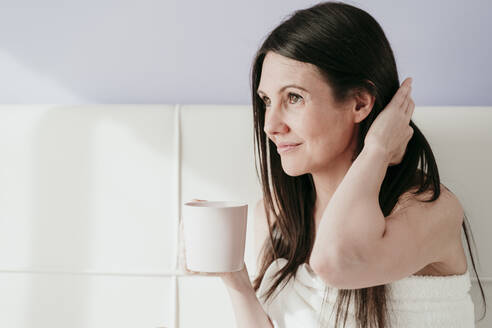 Thoughtful woman holding coffee cup while sitting in bedroom at home - EBBF00998