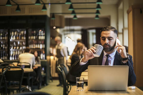 Businessman talking on phone while drinking coffee in restaurant - MASF20058