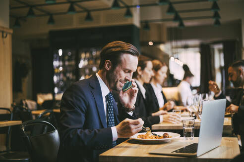 Smiling male business person talking on phone while eating food in restaurant - MASF20067