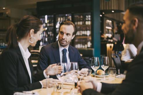 Confident businessman talking to businesswoman in restaurant - MASF20079