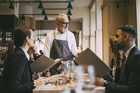 Waiter talking to business people while standing by table in restaurant - MASF20082