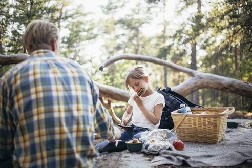 Daughter eating watermelon while sitting with father on picnic blanket in forest - MASF20173