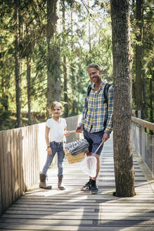 Portrait of father and daughter with picnic basket standing on footbridge in forest - MASF20197
