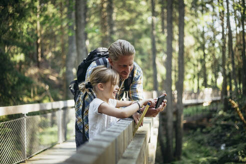Smiling father with backpack and daughter looking at smart phone in forest - MASF20200