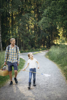 Smiling daughter talking to father holding picnic basket on road in forest - MASF20203