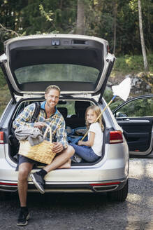 Portrait of smiling father with picnic basket by daughter sitting in car trunk - MASF20209