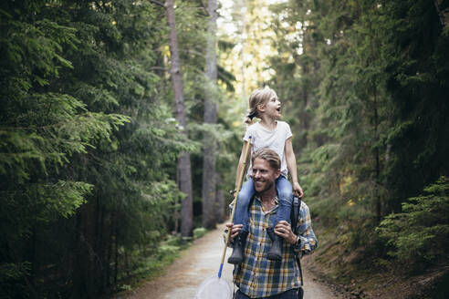 Smiling father carrying daughter on shoulder while walking in forest - MASF20227