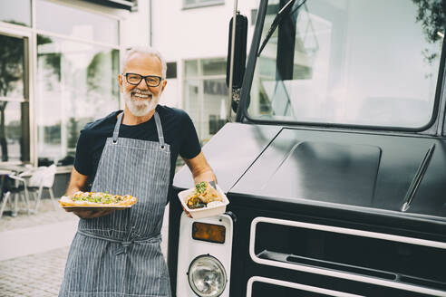 Smiling senior owner with food plate standing against commercial land vehicle - MASF20233