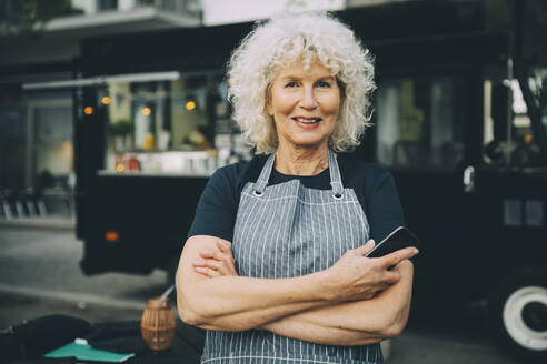 Portrait of senior owner with smart phone standing against food truck in city - MASF20242