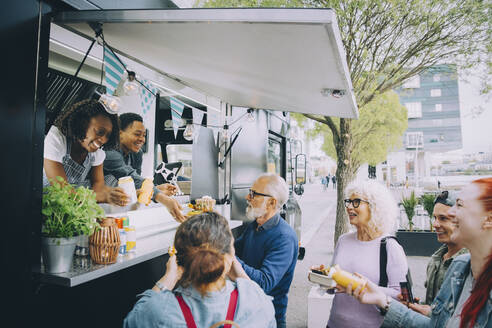 Smiling male and female customers talking to food truck owners in city - MASF20254