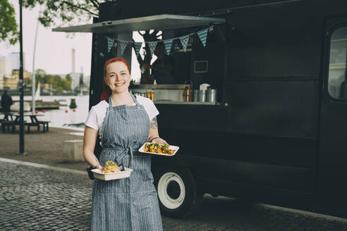 Portrait of smiling female owner holding indian food plate against commercial land vehicle - MASF20278