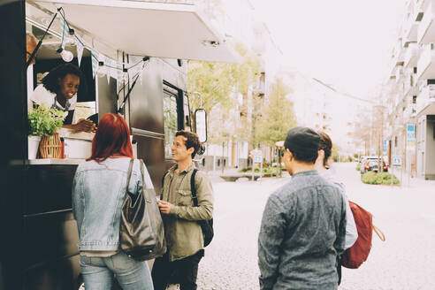 Owner with assistant talking to smiling customers by food truck on street - MASF20293