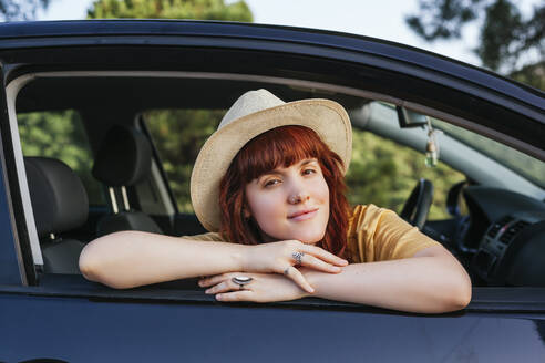 Smiling young beautiful redhead woman leaning out from car window - MGRF00007