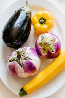 Top view of ripe eggplants and squash in plate placed on table with tomatoes and yellow peppers - ADSF16972