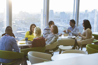Business people eating lunch and socializing in highrise cafeteria - CAIF29713