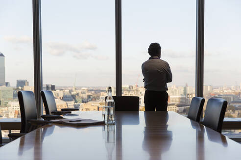 Thoughtful businessman looking out urban conference room window - CAIF29719