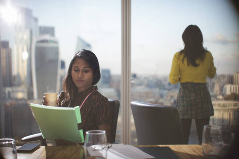 Businesswoman with coffee reviewing paperwork in conference room - CAIF29761