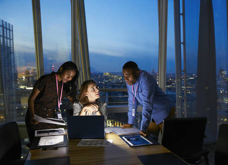 Business people working late at laptop in highrise conference room - CAIF29767