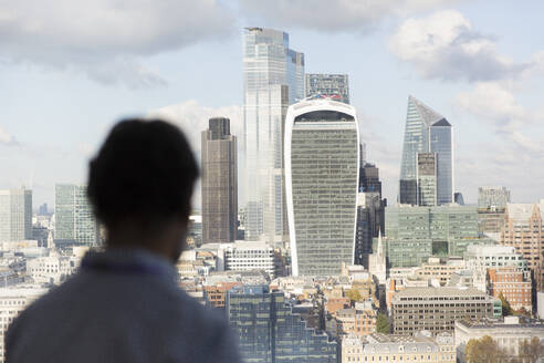Businessman looking at sunny London cityscape from office window, UK - CAIF29782