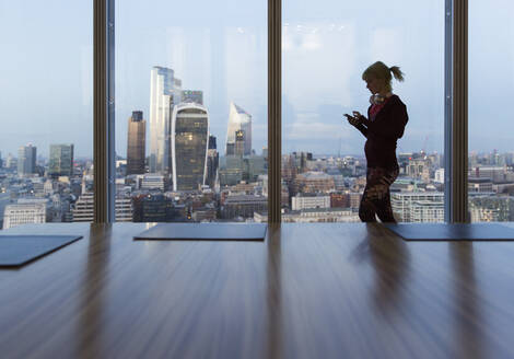 Businesswoman using smart phone at highrise office window, London, UK - CAIF29788