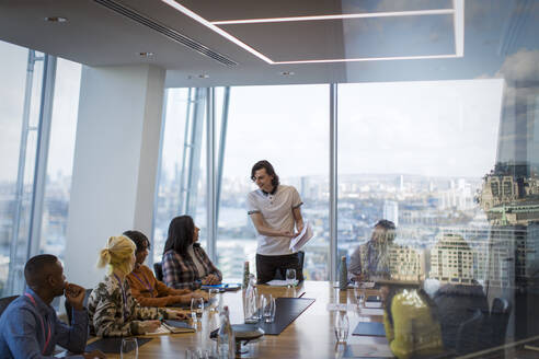 Businessman leading conference room meeting in highrise office - CAIF29812