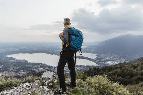 Mature man with backpack looking at lake and city against sky during sunset - MCVF00633