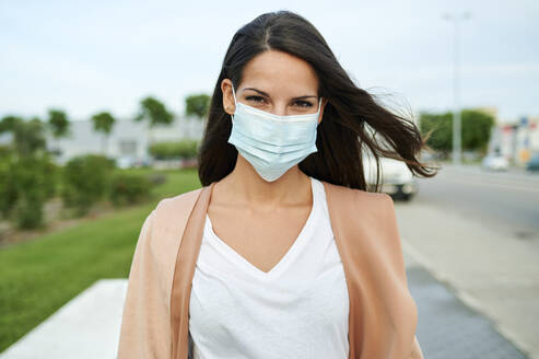 Young woman wearing protective face mask standing on street - KIJF03357