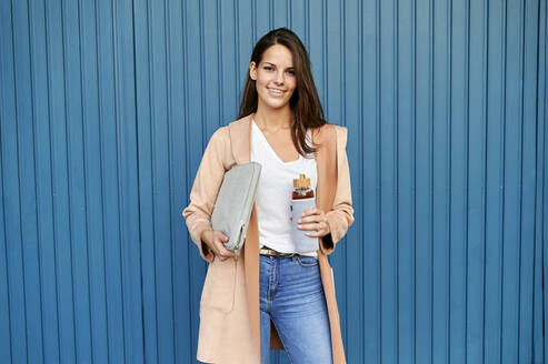 Young woman holding laptop bag and reusable bag while standing against blue metal wall - KIJF03372