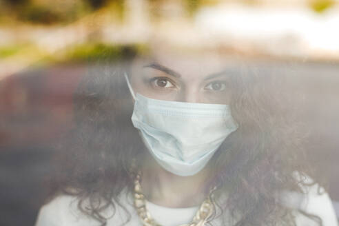 Beautiful young woman wearing protective face mask seen through glass window during COVID-19 pandemic - VYF00151