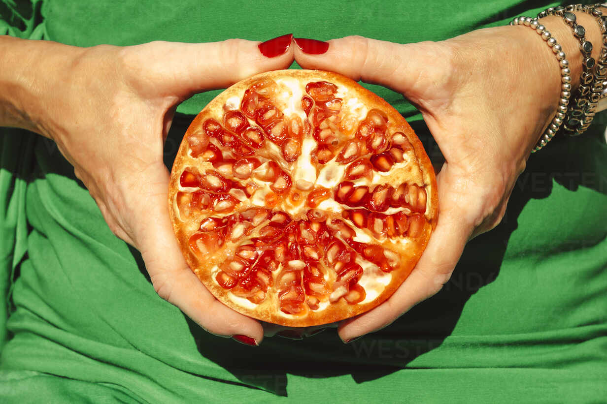 Hands of woman holding halved pomegranate - ERRF04649 - Eloisa Ramos/Westend61