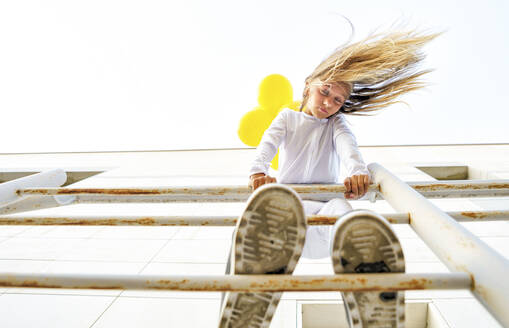 Low angle view of girl standing on railing with tousled hair during sunny day - GGGF00006