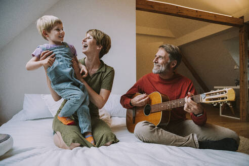 Father playing guitar while mother and son enjoying music while sitting on bed in bedroom at home - MFF06623