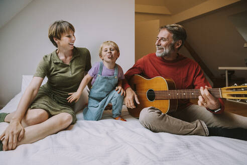 Son sticking out tongue while father playing guitar and mother sitting beside on bed at home - MFF06626