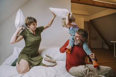 Son sitting on father's shoulder doing pillow fight with mother in bedroom at home - MFF06629