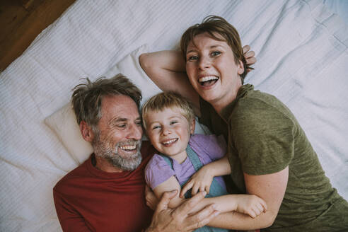 Smiling mother, father and son embracing each other while lying on bed at home - MFF06632