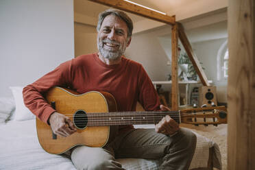 Mature man playing guitar while sitting on bed in bedroom at home - MFF06641