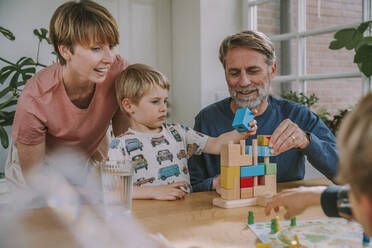 Parents playing with children puzzle at home - MFF06653