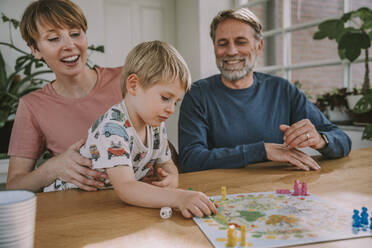 Parents playing board game with son at home - MFF06656