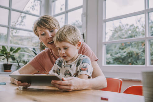 Mother and son using digital tablet while sitting at home - MFF06665