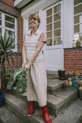 Mid adult woman holding kale leaf while standing in back yard - MFF06668