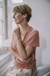 Mid adult woman looking through window with hand on chin sitting at home - MFF06671