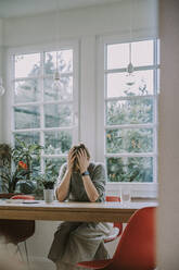 Depressed woman with head in hands sitting at home - MFF06674
