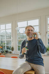 Mature man talking on smart phone while holding beer bottle at home - MFF06686