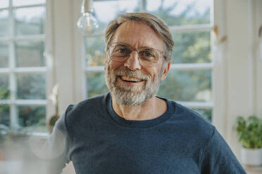 Mature man laughing while standing at home - MFF06698