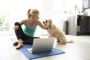 Mature woman sitting on exercise mat using laptop at home - PMF01433