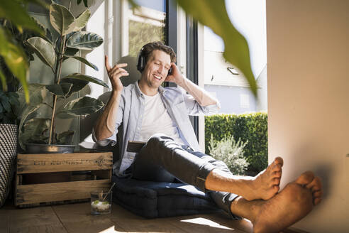 Mid adult man listening music through headphone sitting at home - UUF21874