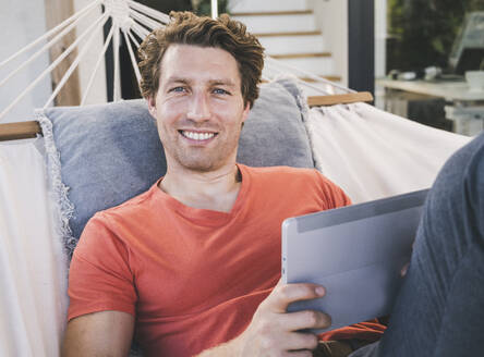 Mid adult man lying in hammock using digital tablet at home - UUF21886