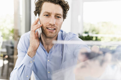 Mid adult man talking on smart phone while sitting in office - UUF21892