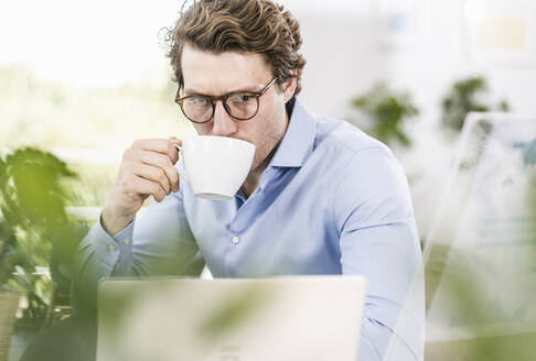 Mid adult man working on laptop while drinking coffee sitting in office - UUF21901