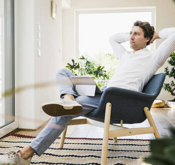 Mid adult man with hands behind head sitting on chair at home - UUF21919